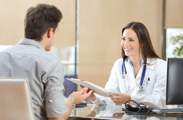 man sitting at female doctor's desk
