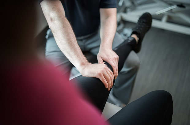 Provider stretching knee of patient