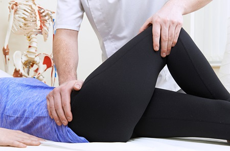 Provider stretching hip of patient