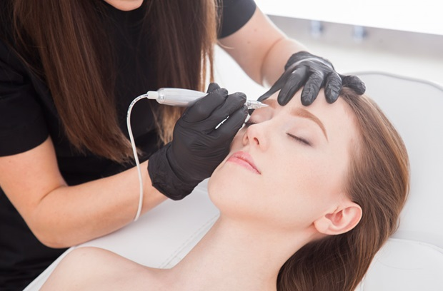 Woman receiving micropigmentation (permanent makeup tattoo) on eyebrows