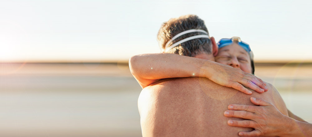 Back view of older couple hugging on beach