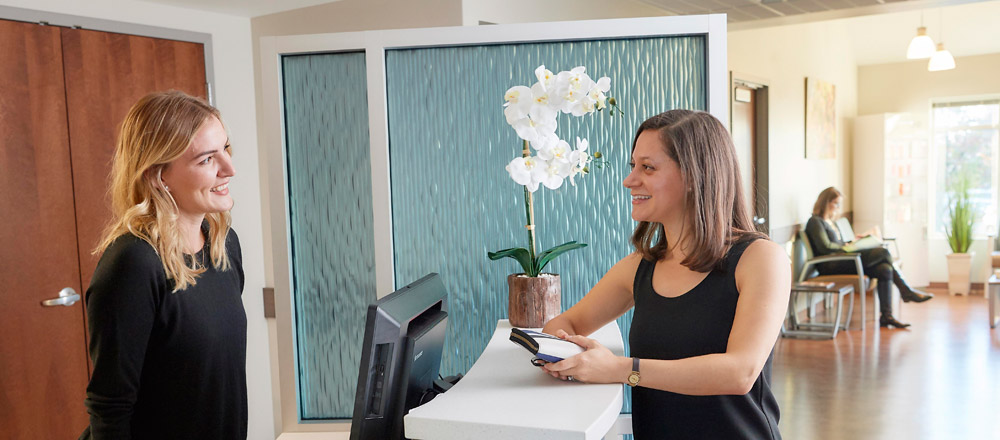 Woman being greeted at Cosmetic Services front desk