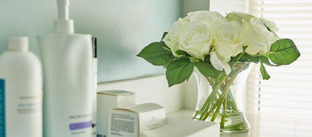 Bathroom counter with skin products and vase of flowers