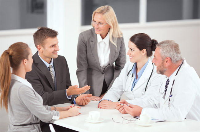 Physicians sitting at table during meeting